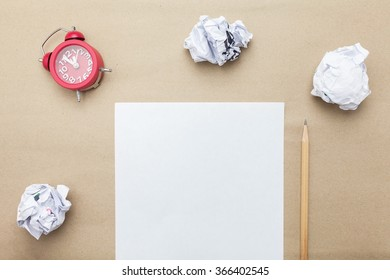 Business concept:red clock,white blank paper,crumpled paper and pencil on brown paper blackground
