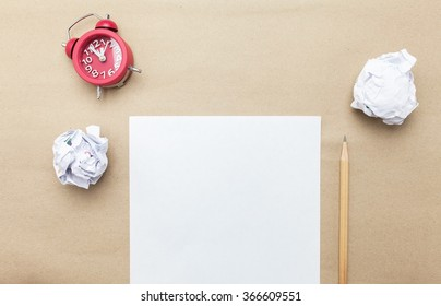 Business concept:red clock,white blank paper,crumpled paper and pencil on brown paper background