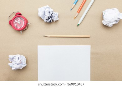 Business concept:red clock,white blank paper,crumpled paper and color pencil,pencil,pen on brown paper background