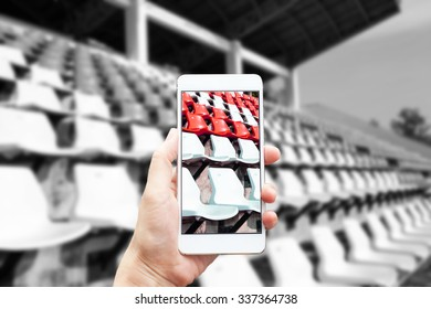 Business conceptual- Focused on left hand holding mobile with stadium blurred background