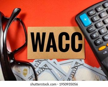 Business concept.Word WACC (weight average cost of capital) with glasses,banknote and calculator on red background.