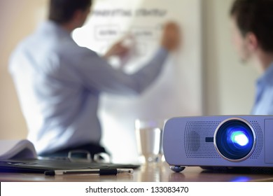Business conference or lecture with businessman writing on whiteboard and lcd projector in foreground