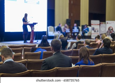 Business Conferences Ideas. Group of People Attending Conference and Listening to the Host Speaker On Stage. Back View of Listeners.Horizontal Orientation