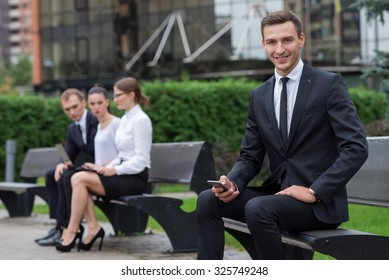 Business confidence. Portrait of motivated businessman. Successful leader is working in business suit. Outdoors business concept. His business partners and colleagues are on the background
