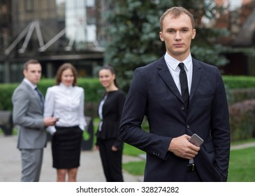Business confidence. Portrait of motivated businessman. Leader is working in business suit. Outdoors business concept. His business partners and colleagues are on the background