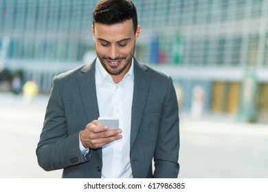 Business confident man using his smartphone
