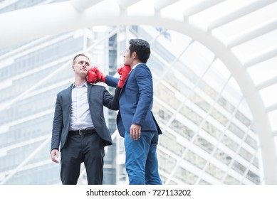 Business conflict. Young man in formalwear  don Boxing gloves for battle with competitor at capital city