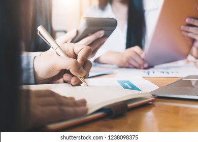 business consulting or finance budget plan, business advisor holding pen pointing to explain method profit with business owner use pen write to notebook and use laptop computer.