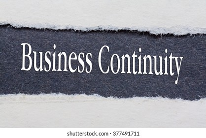 Business continuity words under torn black paper.