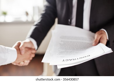 Business contract held by businessman during handshake with partner