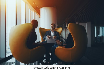 Business conversation between handsome cheerful employer in formal suite and two of his female coworkers sitting in front of each other on curved orange armchairs near window, office with reflections