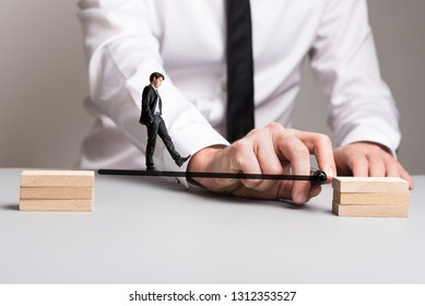 Business cooperation concept - businessman drawing a line from one pile of wooden block to the other for his partner to safely walk across.