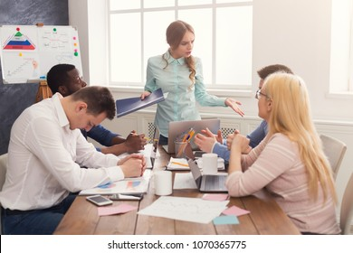 Business corporate meeting of young team with female boss. Angry woman shouting at her guilty workers for failure. Office discussion, communication with partners, copy space