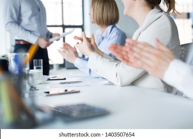 business, corporate and success concept - colleagues applauding to businessman at office meeting or presentation
