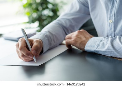 Business correspondence. Cropped shot of man holding pen over blank sheet of paper. Copy space.