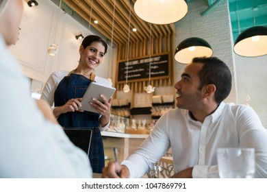 Business couple at a bakery working and friendly waitress taking their order on a digital tablet smiling very happy