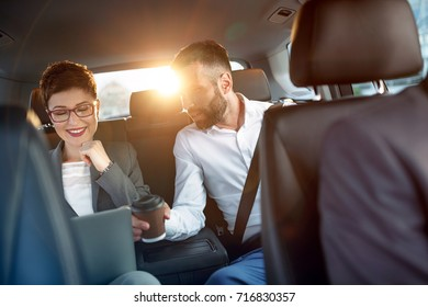 Business couple in the car going on business trip