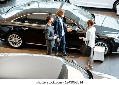 Business couple chosing a new car standing with salesperson in the car showroom. View from above
