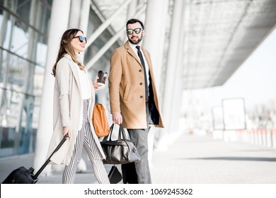 Business couple in coats walking out the airport with luggage during the business trip