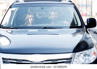 Business couple having a conversation while driving a car. Front view through the windshield