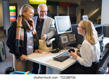 Business Couple Looking At Staff Holding Passport At Airport Che