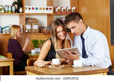 Business couple looking together at tablet computer in a caf�©