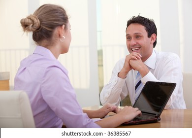 Business couple at an office working on a laptop