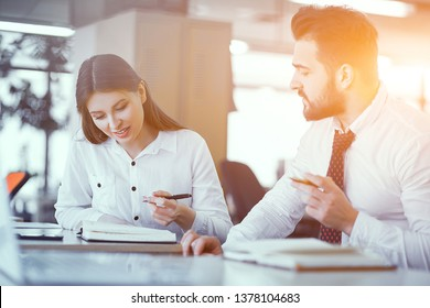 Business Couple With Pens And Notebooks Having Brainstorm In Sunny Modern Office. Business Concept.