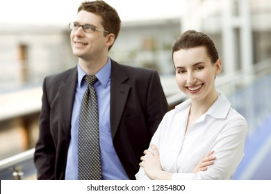 Business couple portrait - young man and woman on modern office corridor