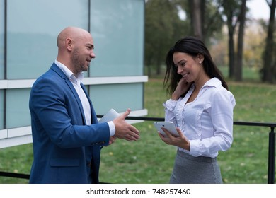 Business couple shaking hands near the office outdoor