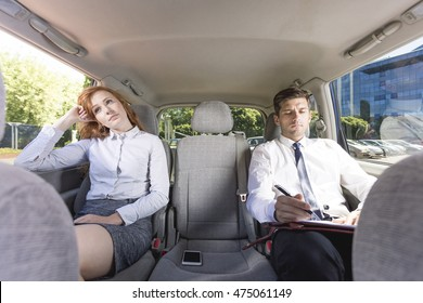 Business couple sitting on a back seat of a car