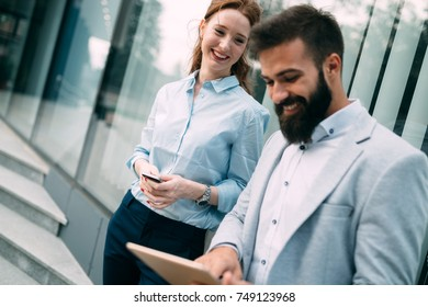 Business couple using digital tablet in front of office