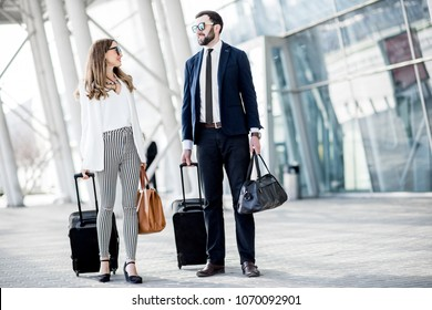 Business couple walking with luggage near the airport during the business trip