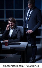 Business couple working at office at night, woman sitting beside desk, talking on cellphone