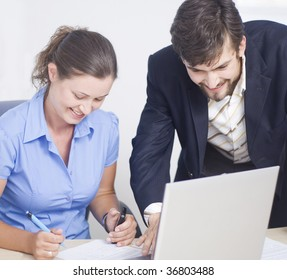 Business couple working on a laptop and sign document