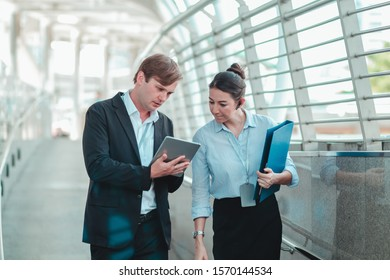 Business couples are discussing business issues while walking on the skywalk Both are busy working all day. And still holding the file with the tablet all the time
