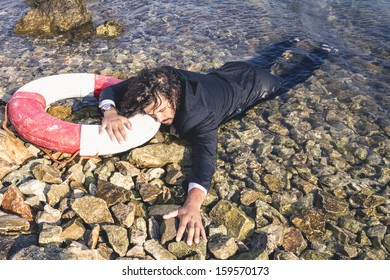 Business Crash. Man out of conscious at the beach washed by the sea.