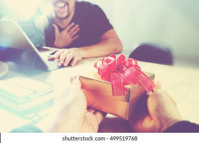 business creative designer hand giving his colleague Christmas present in office,vintage effect