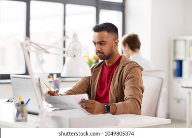 business and creative people concept - young indian man with laptop computer and papers working at office