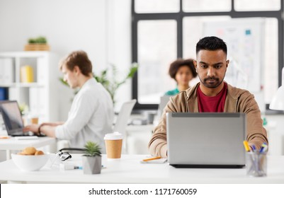 business and creative people concept - young indian man with laptop computer working at office