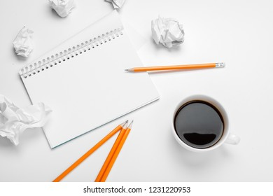 business creativity concept. Coffee, sheets of paper and crumpled wads on table