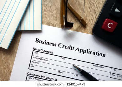 Business credit application form with pen, calculator and glasses on desk