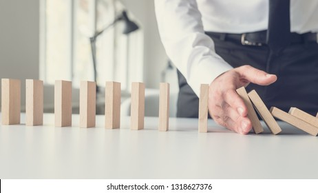 Business crisis management concept - business mediator stopping falling dominos with his hand.