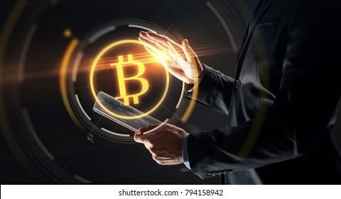 business, cryptocurrency and future technology concept - close up of businessman with transparent tablet pc computer and virtual bitcoin symbol hologram over black background