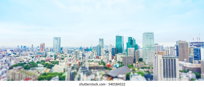 Business and culture concept - panoramic modern city skyline bird eye aerial view from tokyo tower under dramatic morning blue cloudy sky in Tokyo, Japan. Miniature Tilt-shift effect