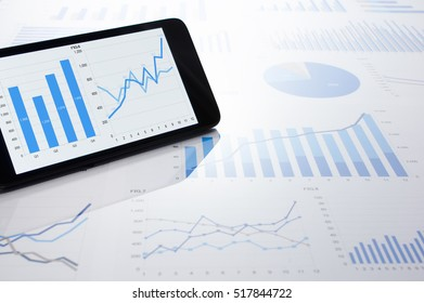 Business data, charts and smartphone. Many charts and graphs. Reflection light and flare.