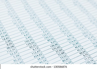 Business data report selective focus close up. Monthly stock stats spreadsheet. Blue toned.