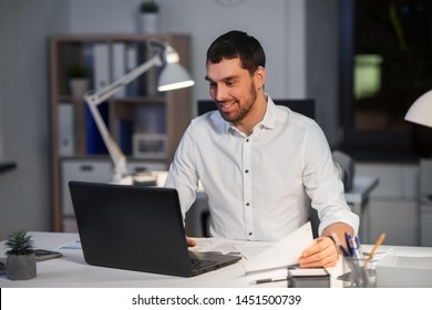business, deadline and people concept - businessman with laptop computer and papers working at night office