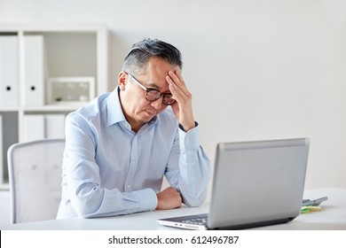 business, deadline, stress, people and technology concept - businessman in eyeglasses with laptop computer suffering from headache at office