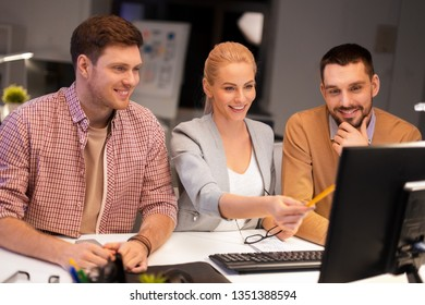 business, deadline and technology concept - coworkers with computer working late at night office